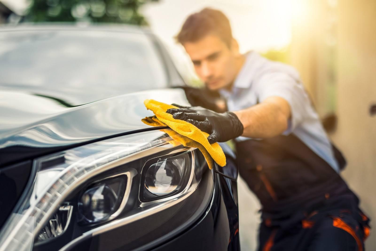Un detallista encera el costado de un automóvil con una microfibra.
