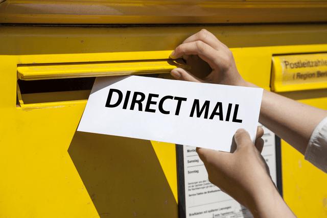 Una imagen de alguien que coloca una pieza de correo directo en un buzón.